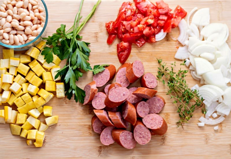 Summer Squash and Smoked Sausage Skillet Ingredients on a wood cutting board - white beans, diced summer squash, sliced smoked beef sausage, chopped red tomatoes, sliced white onions, and fresh parsley and thyme