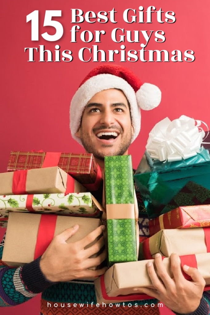 Man wearing a Santa hat and holding a pile of gifts. Above is test which reads: 15 Best Gifts for Guys this Christmas. At the bottom is text which says HousewifeHowTos.com
