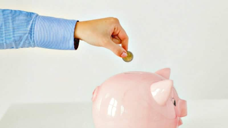 Man in a blue shirt stretches his hand to deposit coins in a pink piggy bank