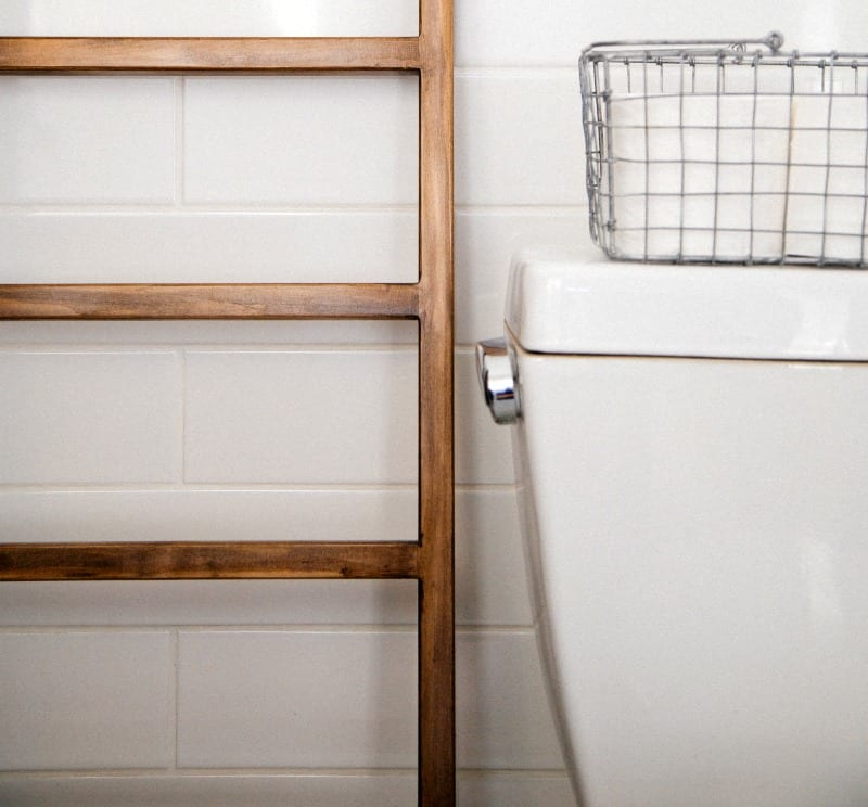 Towel ladder in a white bathroom next to a toilet where there are things you should not flush