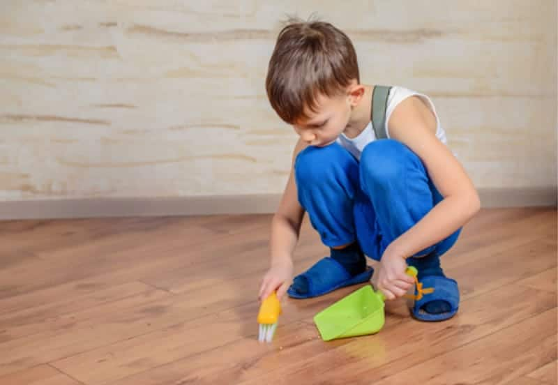 Young boy using a hand broom and dust pan to show chores that kids can do