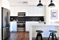 Get an Organized and Clean Home - A clean and modern white kitchen with dark wood floors