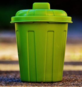 How to Clean Trash Cans and Deodorize Them Naturally - Green garbage can on sidewalk