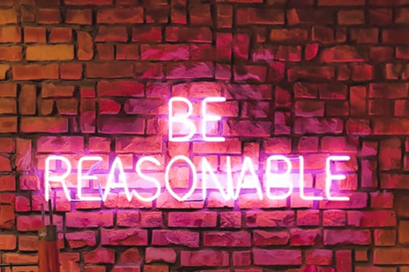 Organizing kids closets - Neon wall sign says 'Be Reasonable""