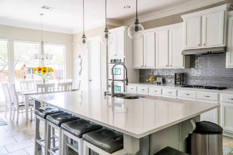 Get an Organized and Clean Home - A clean, uncluttered kitchen with white cupboards and a shiny quartz island countertop