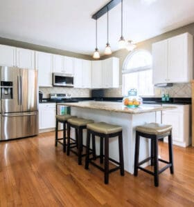 Clean kitchen with white cupboards and a hardwood floor
