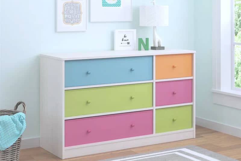 Organizing kids dressers - a white dresser with bright sherbert-colored drawers in a pale blue bedroom