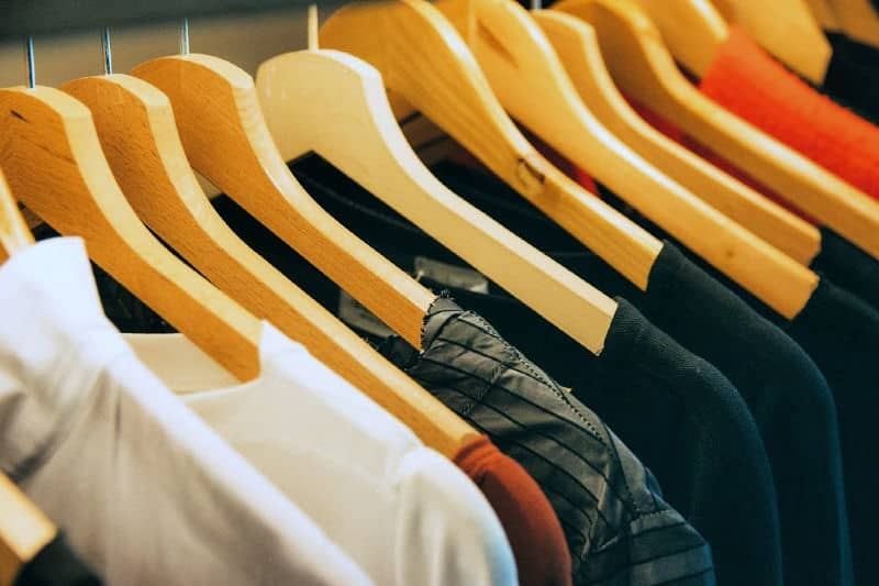 Organizing bedroom closets - Clothing sorted by color and hung on matching wood hangers