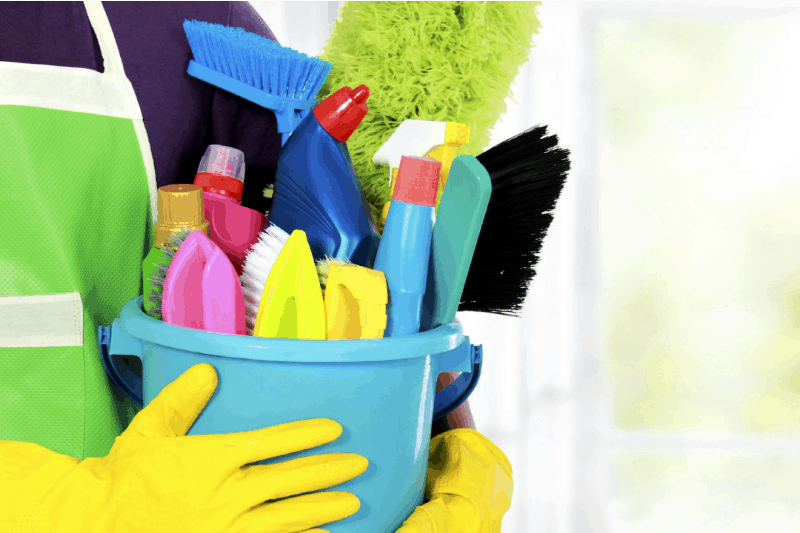 Organizing Cleaning Supplies - Woman wearing cleaning apron and rubber gloves holds a bucket of cleaning supplies and small brushes