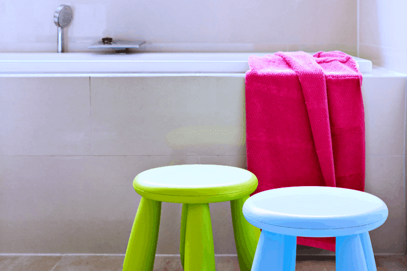 Organizing Kids Bathrooms - Blue and footstools in front of bathtub draped with a bright pink towel