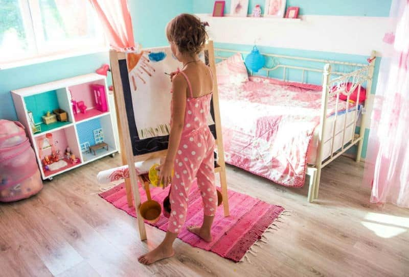 Organizing Kids Bedrooms - Think in zones - Little girl painting in the play zone