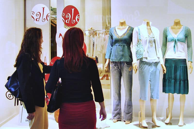 Organizing Tips to Keep Clutter Away - Two women looking through a window at clothing on sale
