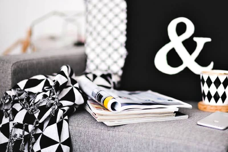 Organize bedrooms in zones - A reading chair with magazines, a blanket, and pillows