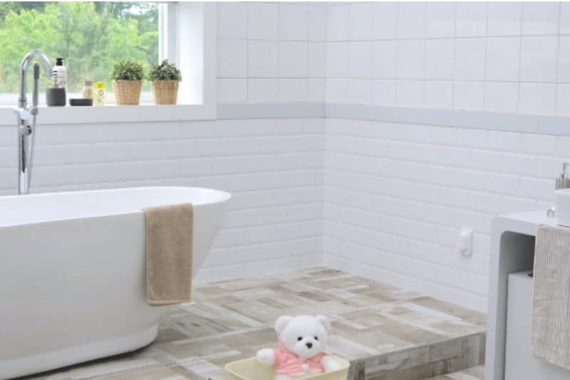 Organizing kids bathrooms - a clean white bathroom with a teddy bear out of place on the floor
