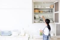 Woman organizing kitchen cupboard