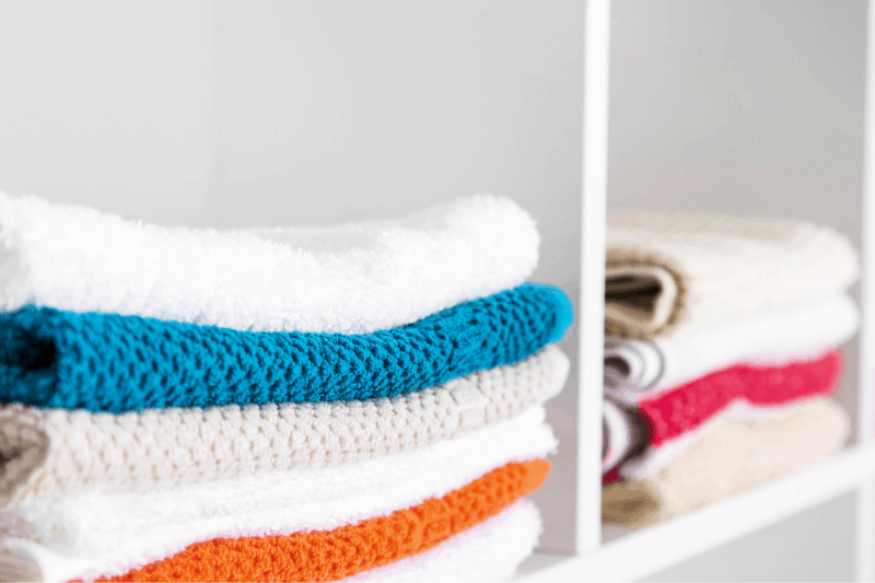 Organizing Linen Closets - Neatly folded towels on a shelf with dividers