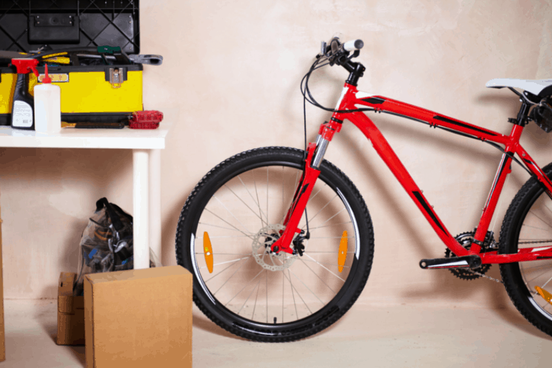 Organizing Garages - Tools on a table with a cardboard box on the floor next to a bike