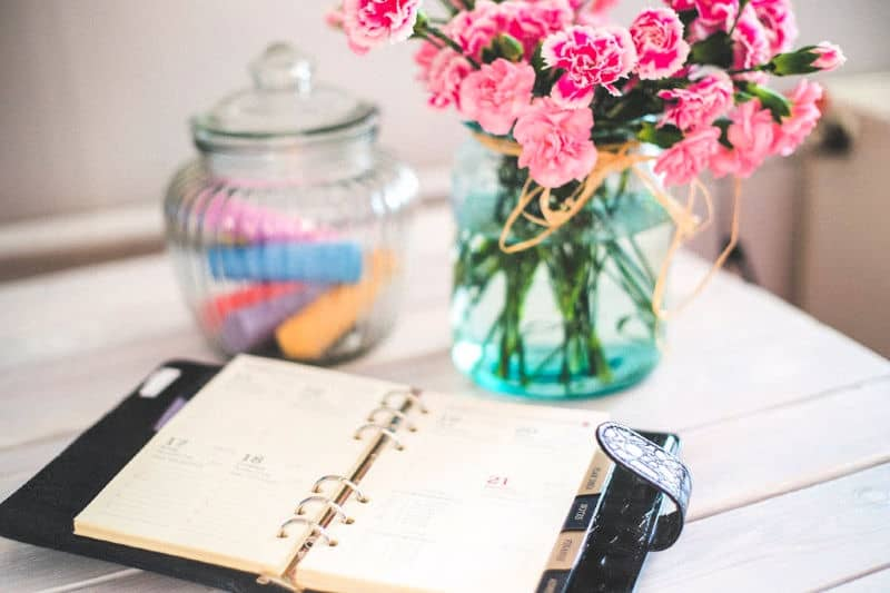 Stay Decluttered with this Schedule - A personal calendar on a desk next to flowers
