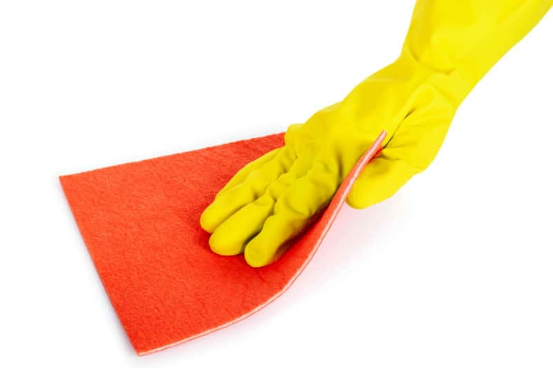 Weekly Cleaning - Hand in rubber glove using a cleaning cloth to wipe a surface