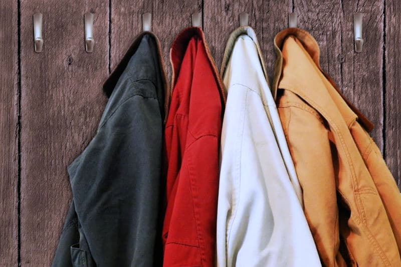 Organizing Tips to Keep Clutter Away - Coats hung on hooks mounted on a wood wall