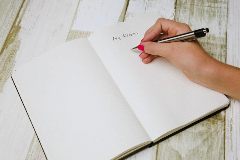 "Organizing Tips to Keep Clutter Away - Woman writing ""My Plan"" in a notebook"