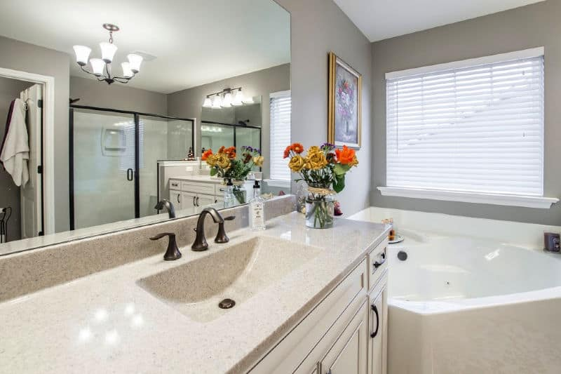 Organizing the Master Bathroom - Neutral colored bathroom with vase of flowers on the vanity