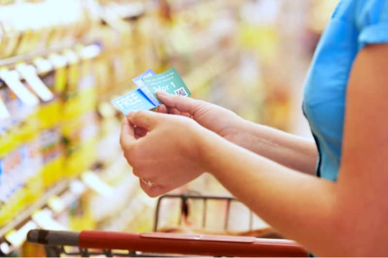 How to Use Coupons - Woman in grocery store holding up coupons