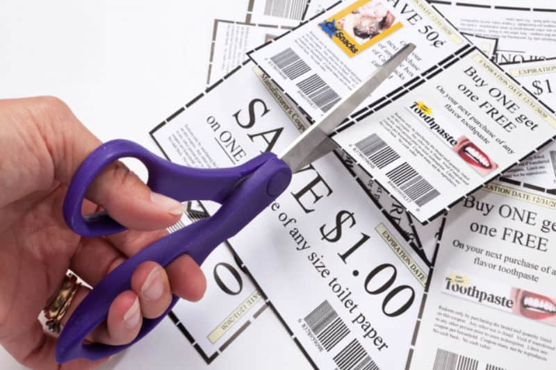 How to Use Coupons - Woman using scissors to cut paper coupons
