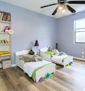 How to Help Kids Organize their Rooms - Twin beds and bookcases in a tidy bedroom