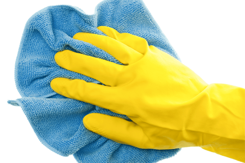 Hand in rubber glove holding damp microfiber cloth