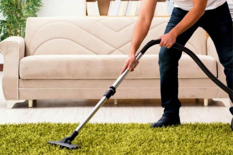 Man vacuuming shag rug