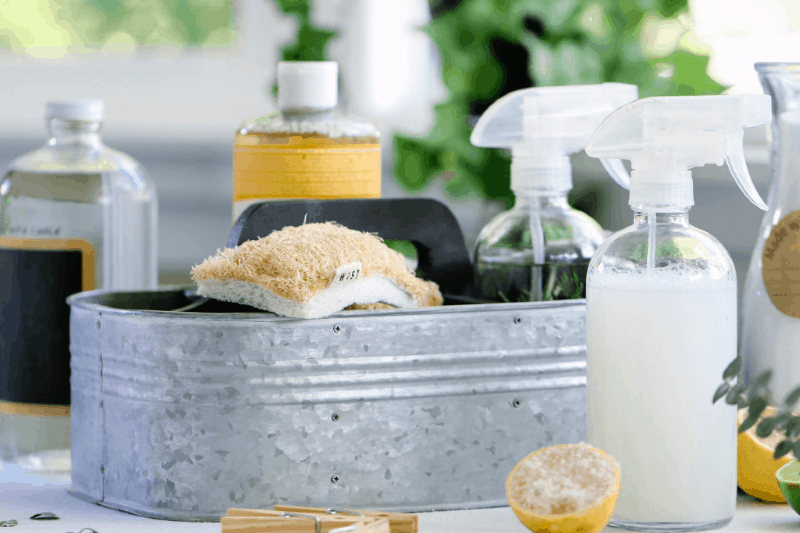 Galvanized bucket holding natural sea sponge and spray bottles of homemade cleaning products