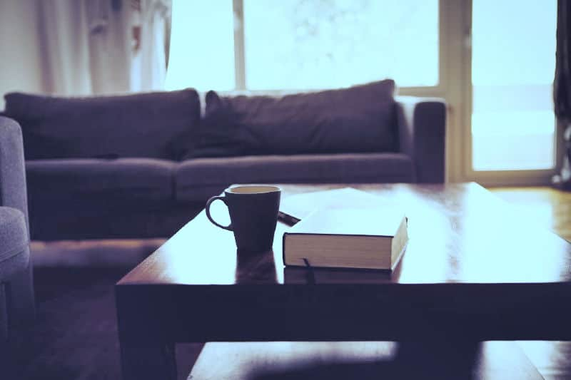 Clean wood coffee table with book on it