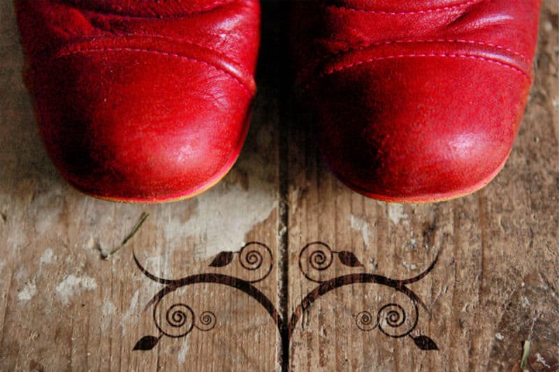 Removing shoe odor by airing out red leather boots on wood floor