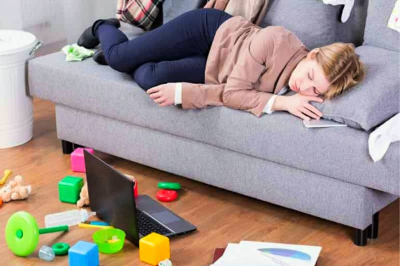 Woman on sofa surrounded by mess who needs to find cleaning motivation