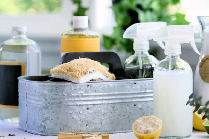 Spray bottles of cleaning supplies grouped in a galvanized caddy to make cleaning faster