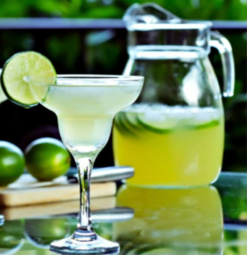 Pitcher of margaritas and one on the rocks with a wedge of lime
