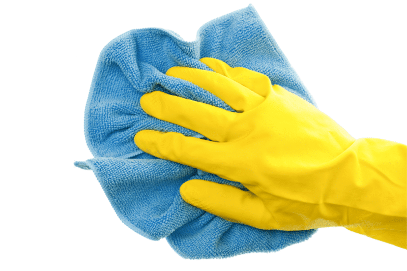 Hand wearing rubber glove holding microfiber cloth