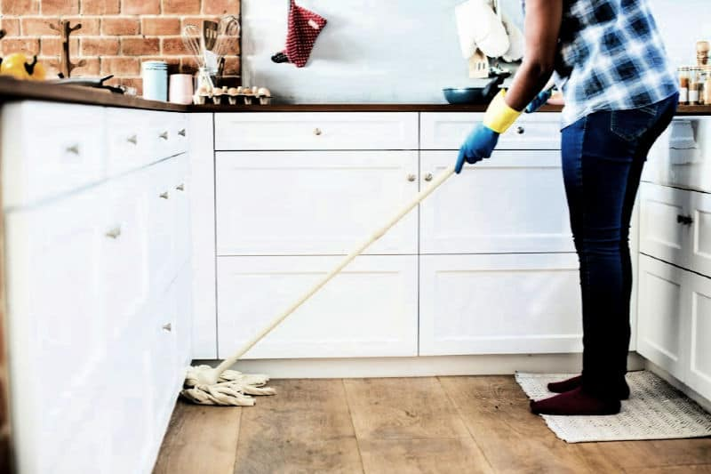 Person mopping wood floor in kitchen
