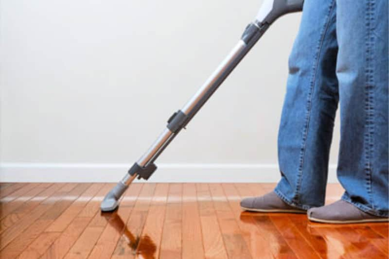 Person vacuuming wood floor