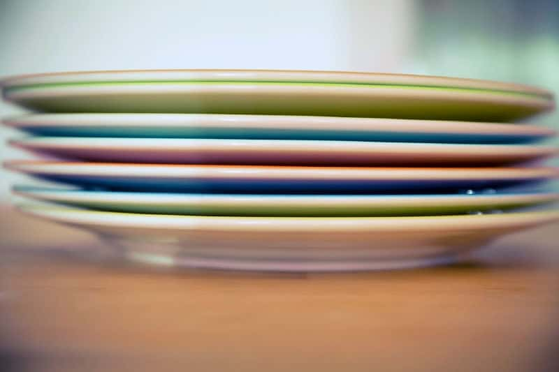Pile of plates after decluttering kitchen cupboard