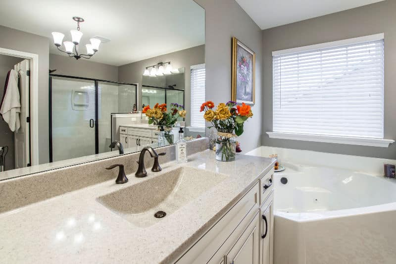 Clean bathroom counter with vase of flowers