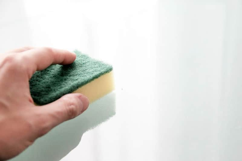 Become a Cleaner person by wiping kitchen messes nightly - hand holding sponge and cleaning counter