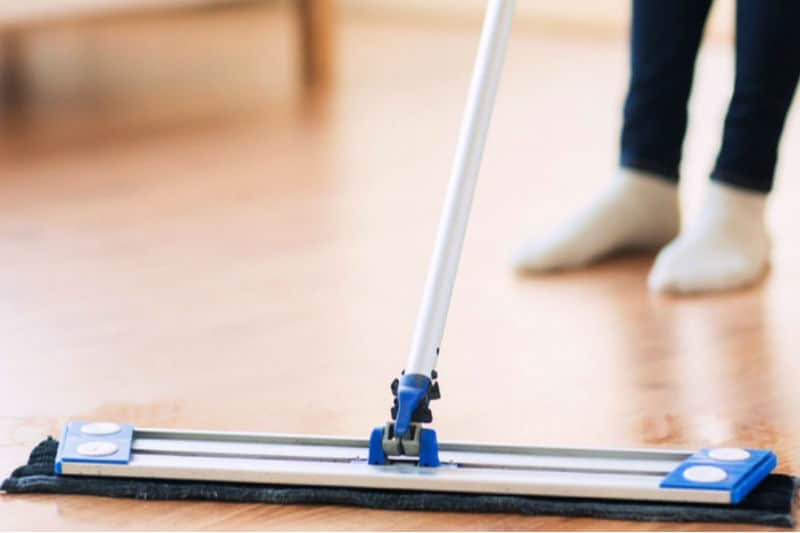 Person in socks dry mopping wood floor