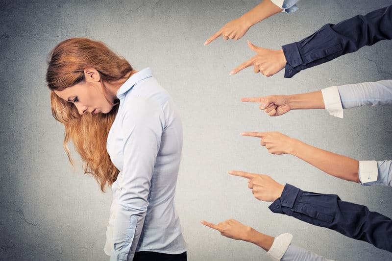 Woman hanging head as fingers point at her