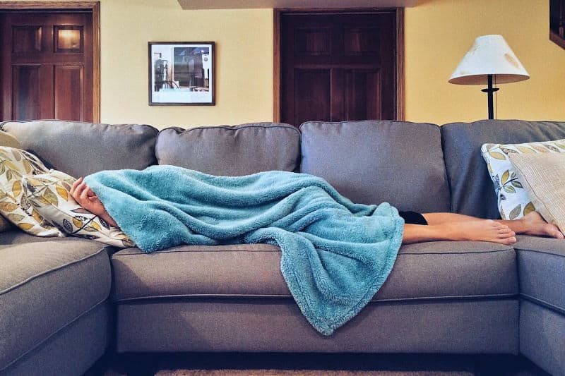 Sick person on sofa under blanket