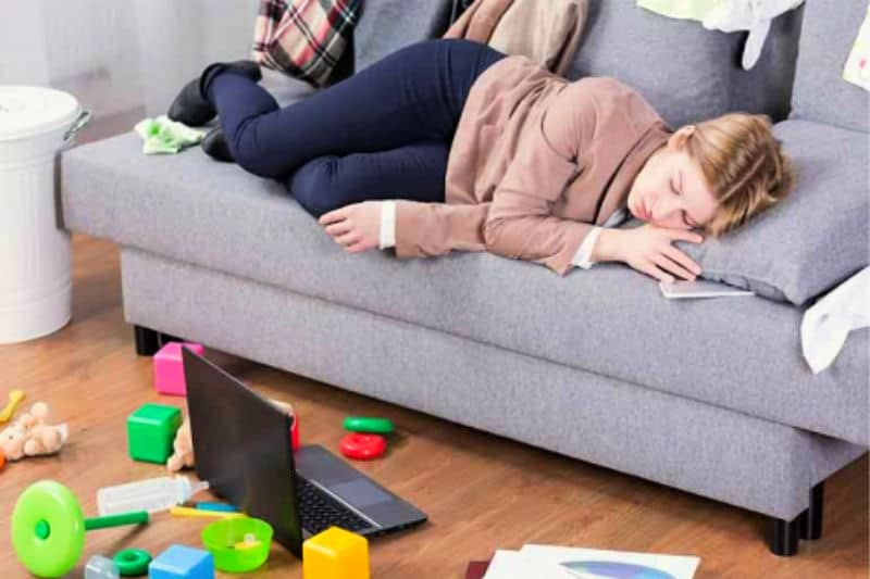 Tired Woman on Sofa Surrounded by Mess