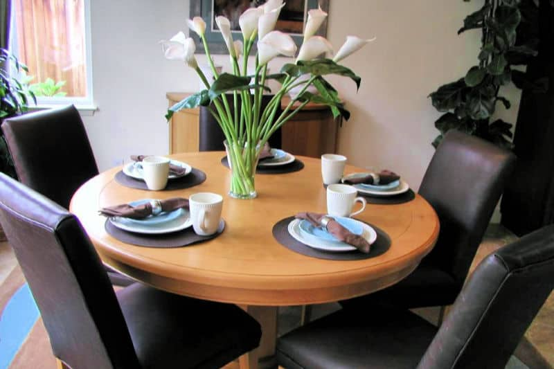 Round light wood dining table and upholstered chairs