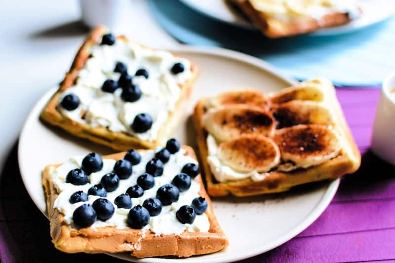 Waffles topped with cream cheese, blueberries and bananas