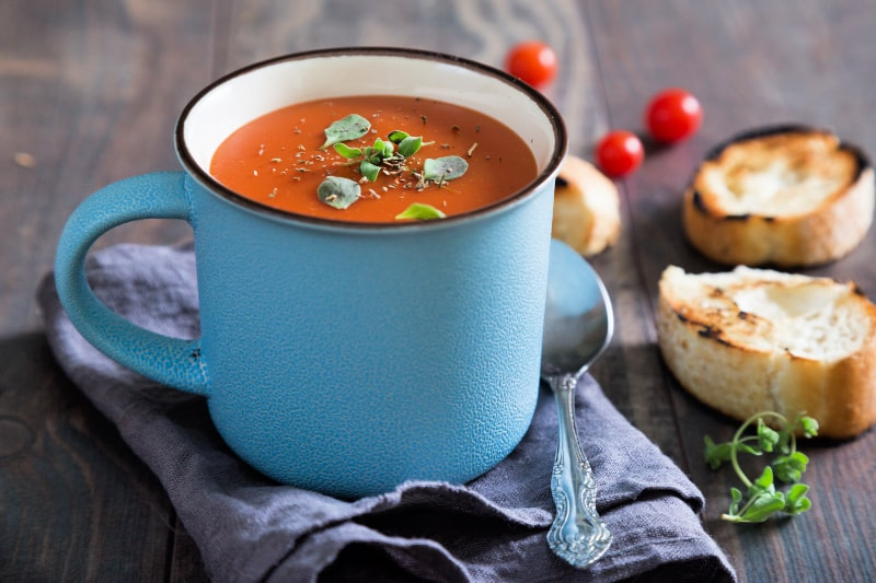 Homemade tomato soup served in mug for easy sipping